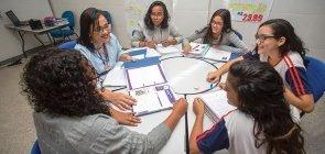 Cinco alunas prestam atenção em uma professora em uma mesa redonda. A professora segura um fichário. As alunas vestem uniforme, três delas também usam casaco cinza