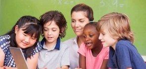 Professora e alunos realizam atividade com computador em sala de aula