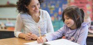 Uma professora sentada ao lado de uma aluna de cerca de 5 anos que está segurando um lápis e escrevendo. As duas estão sorrindo