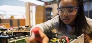 Menina com óculos de proteção mexe com circuitos eletrônicos em sala de aula de aprendizagem criativa