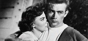 Fotografia em branco e preto. São dois jovens, o homem abraça a mulher e olha para o lado, ela olha para ele