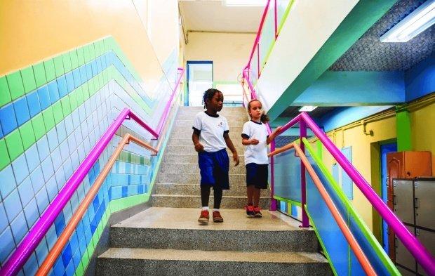 Duas meninas vestindo o uniforme descem a escada. Com as paredes e o corrimão coloridos, o teto tem forro acustico