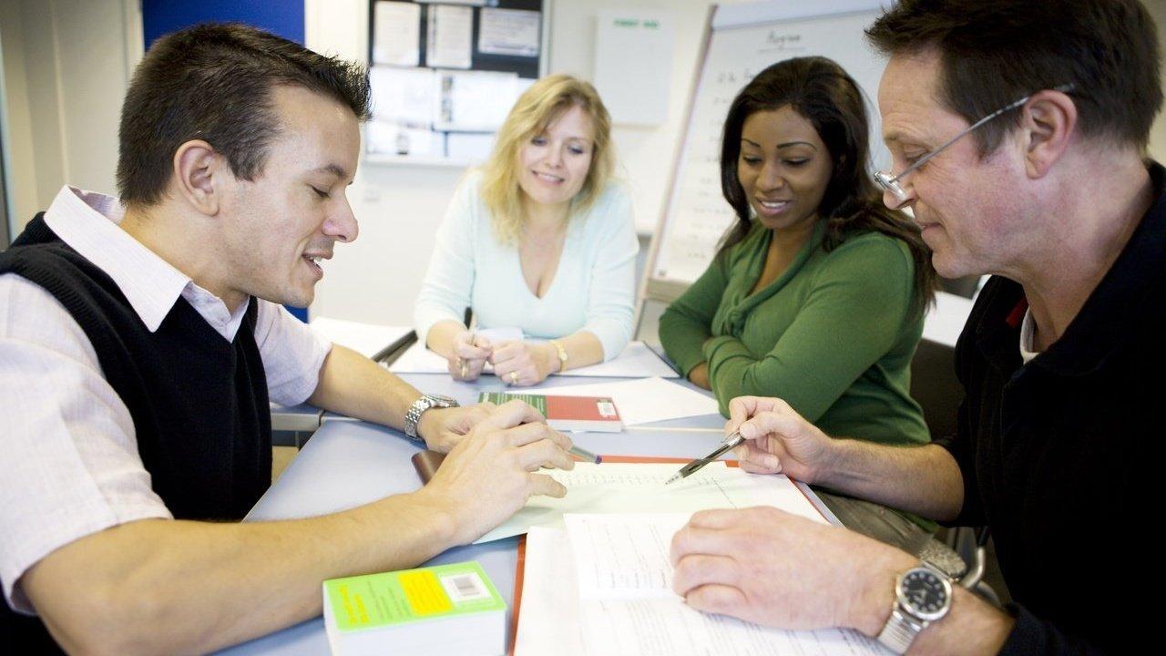 quatro adultos conversam reunidos em uma mesa com papeis