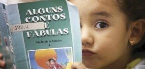 Menina pequena com um livro de contos e fábulas na frente