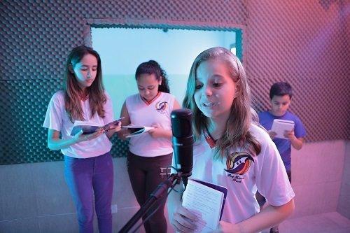 Num estúdio de rádio, uma menina de cerca de 13 anos está a frente do microfone segurando um livro fino. Outras duas estudantes e um estudante estão atrás lendo o mesmo livro.