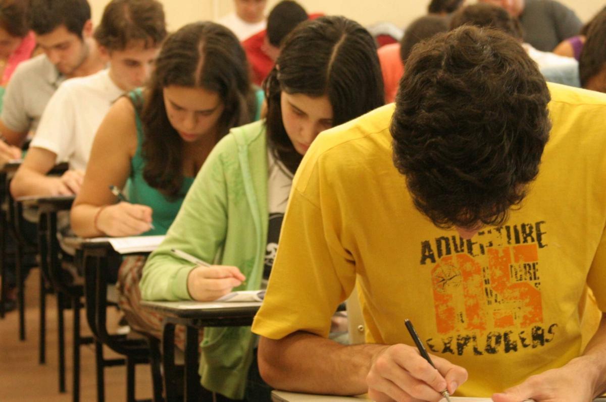 Estudantes adolescentes curvados sobre mesas fazendo provas