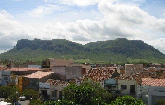 Vista de casas em primeiro plano com serra ao fundo