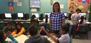 Uma mulher de cerca de 40 anos de pé ao lado de diversos grupos de alunos sentados e trabalhando em grupos