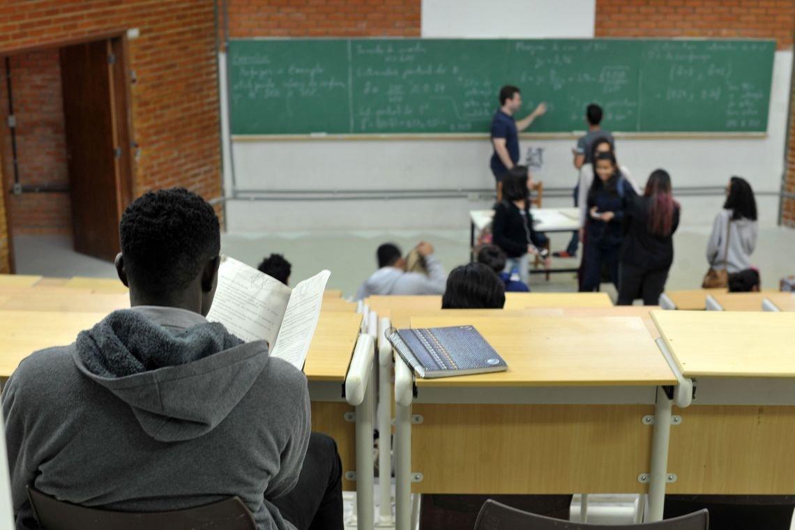 Jovens em uma sala de aula com várias cadeiras vazias e uma lousa com várias inscrições, um jovem negro é visto de costas em primeiro plano