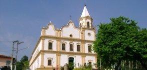 Igreja Matriz de Santana do Parnaíba, com detalhes amarelos perto de uma praça com árvores e carros estacionados.