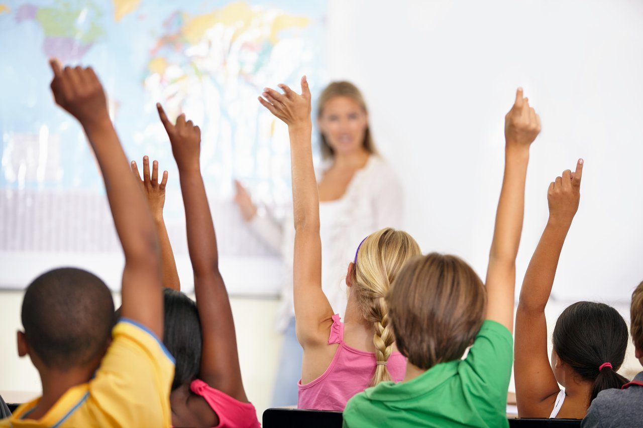 Crianças, de costas para a câmera, levantam a mão para a professora em sala de aula