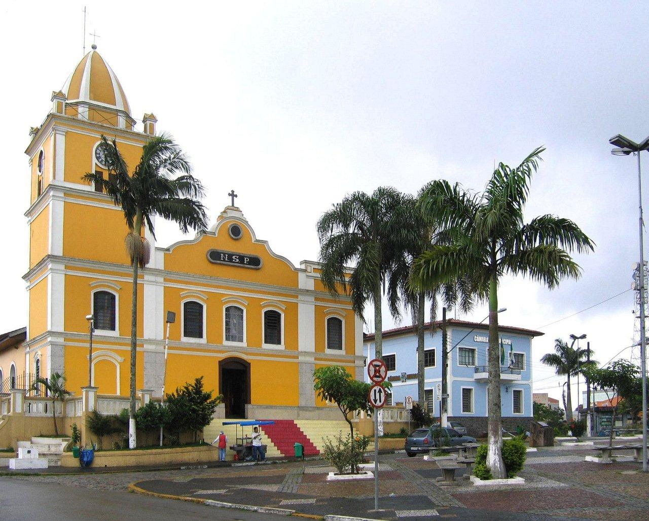 Igreja amarela com detalhes brancos e tapete vermelho na escadaria