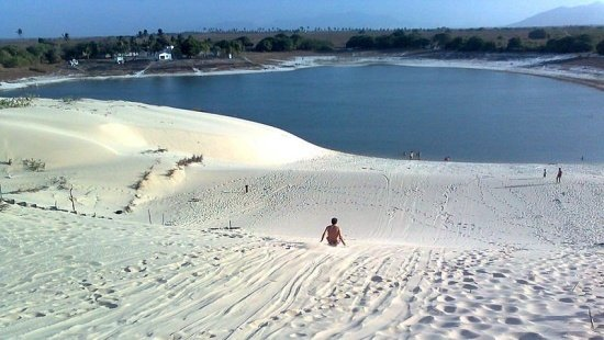 Duna de areia branca que termina em um lago azul com uma pessoa ao centro da foto escorregando rumo ao lago