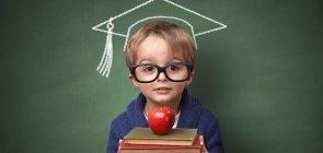 Menino de óculos segurando uma pilha de livros e uma maçã