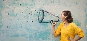 Mulher faz a expressão de estar gritando. Na parede de fundo está desenhado um megafone