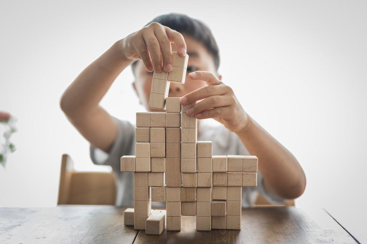 menino montando algo com peças de madeira