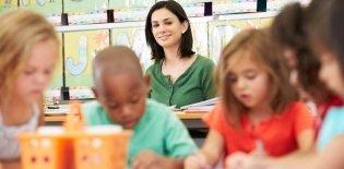 Professora observa alunos em sala de aula