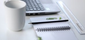 Um notebook ao lado de um bloquinho de papel, um lápis e uma caneca