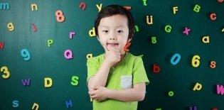 Um menino asiático de cerca de 5 anos com a mão no queixo, como se estivesse pensando pra responder