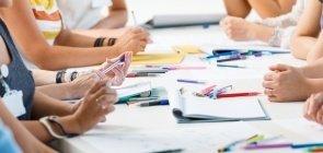 Mãos sobre uma mesa com lápis, canetas e folhas de papel
