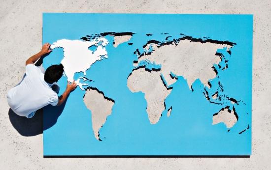 Adulto encaixa a América do Norte em uma grande mapa-múndi colocado no chão