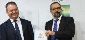 Ministro Abraham Weintraub segurando o caderno da Política Nacional de Alfabetização. Ao seu lado, o secretário de alfabetização do MEC, Carlos Nadalim