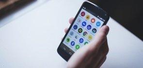 Uma pessoa segura um smartphone com a tela acesa e vários ícones