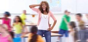 Professora angustiada em sala de aula cercada por alunos ruidosos e mostrados fora de foco