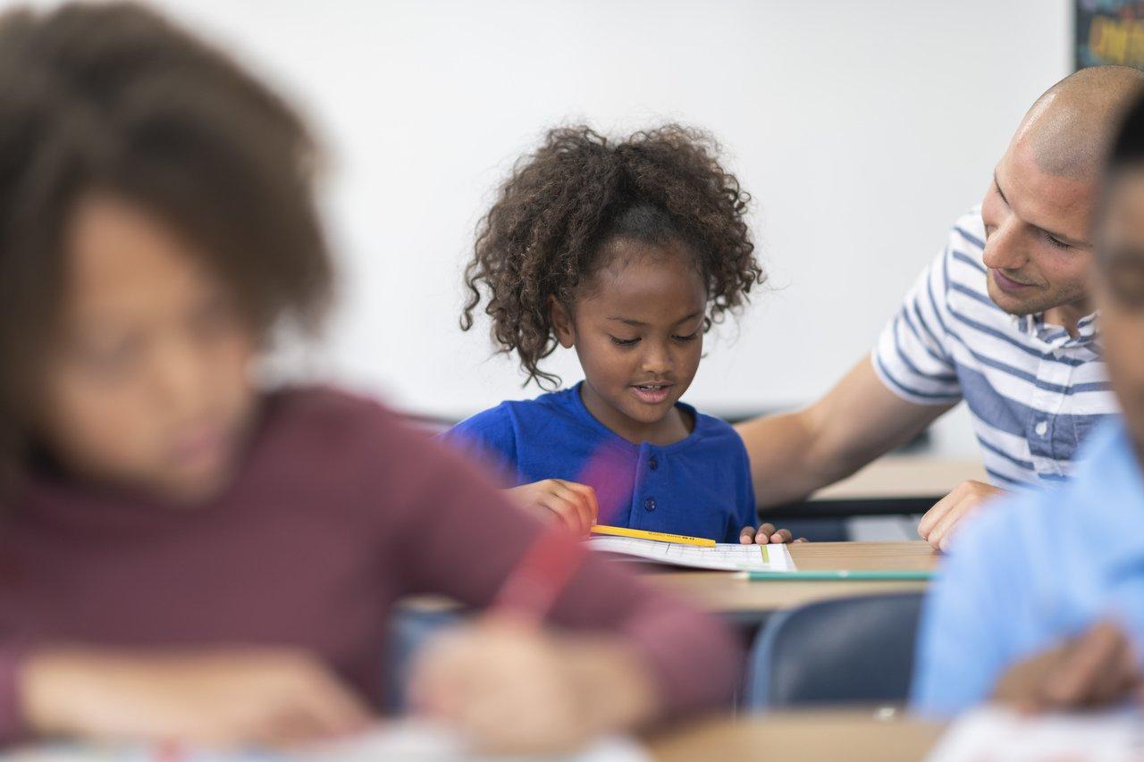 Aluna sentada em uma carteira recebe orientações do professor, os dois estão em segundo plano, com o primeiro plano desfocado