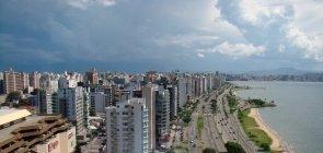 Avenida Beira Mar, a principal avenida do município. Vê-se uma faixa de prédios e construções, três grandes pistas de carros e o mar à direita