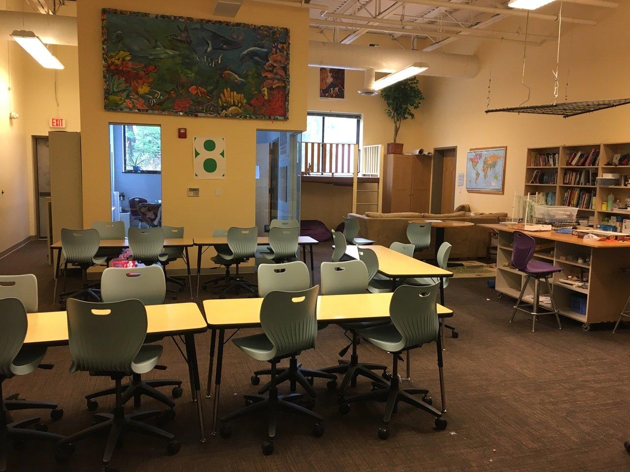 Acera School. Na imagem, vemos uma sala de aula com mesas grandes e dispostas em formato de U.