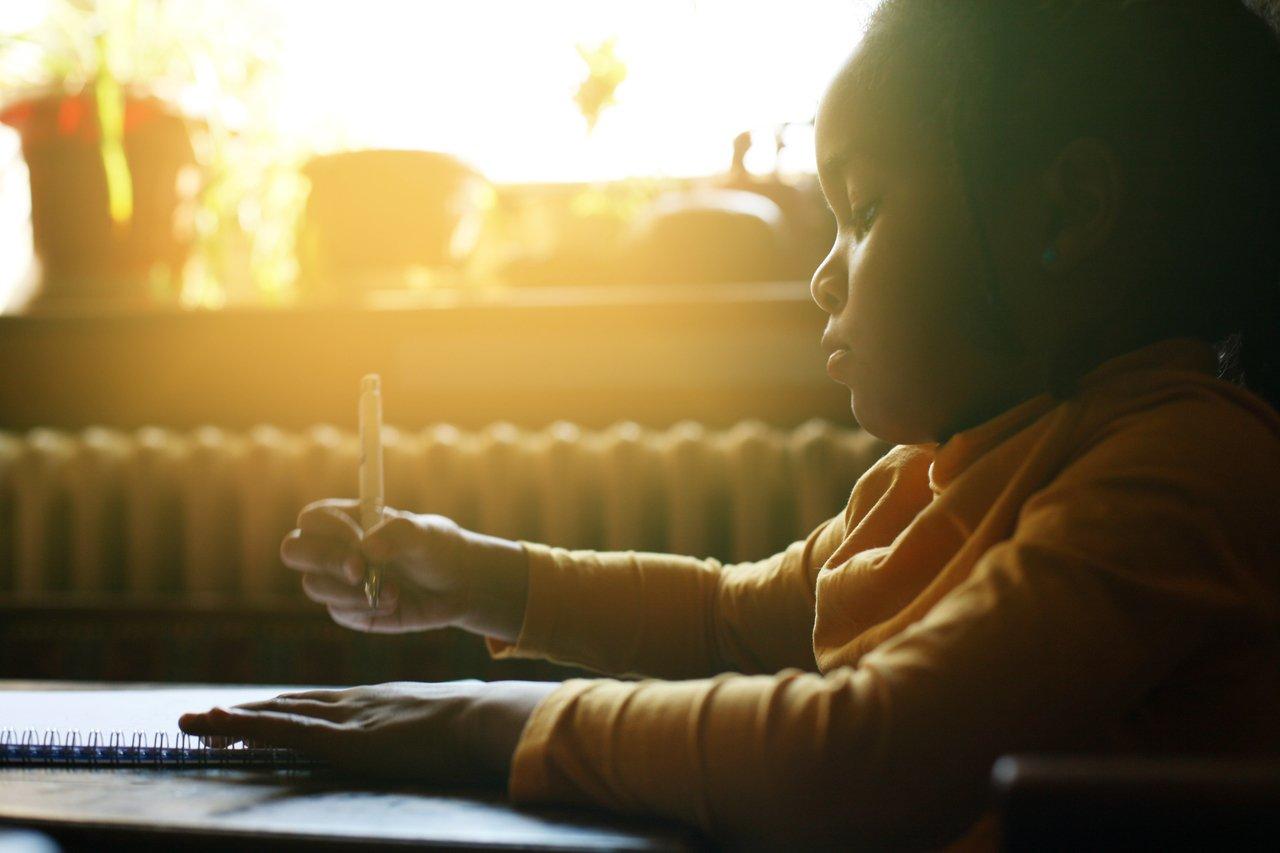 Aluna escrevendo sentada em uma carteira, de perfil, com o sol brilhando