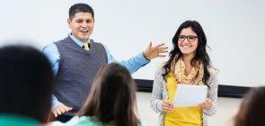 Um homem apresentando uma mulher para a sala de aula