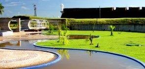 Um gramado com um lago artificial curvolíneo