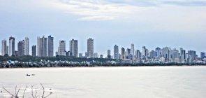 Skyline e beira mar de João Pessoa com prédios e algumas casas à beira da praia