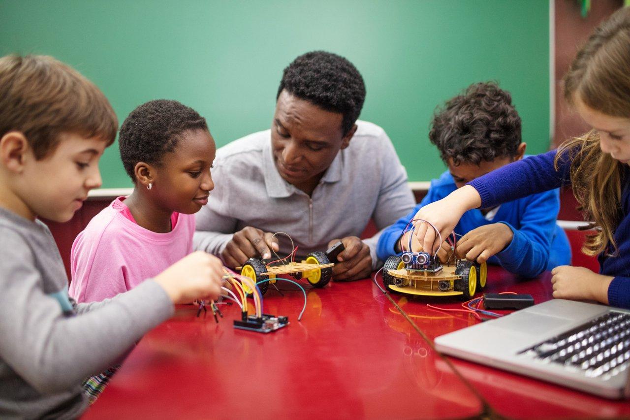 Professor negro cercado de alunos em uma mesa vermelha com um computador e aparelhos de robótica
