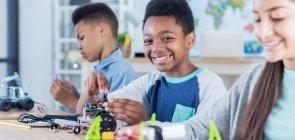 3 alunos mexem com peças, em uma mesa, para montar projetos de robótica