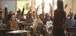 Sala de aula, alunos sentados levantam a mão, professora está de costas para a foto e olha para eles