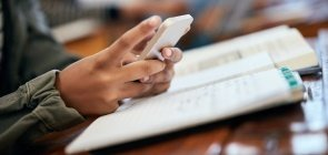 Mãos de um menino de cerca de 12 anos sobre a carteira escolar segurando um celular