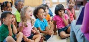 Crianças se divertem ouvindo o professor ler uma história em sala de Ensino Infantil