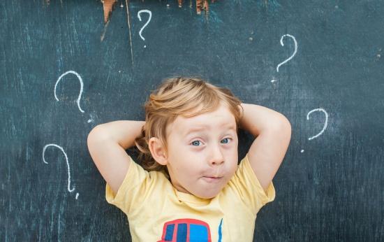 Criança ruiva deitada sobre lousa com vários pontos de interrogação escritos ao seu redor