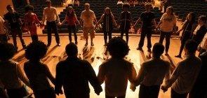 grupo de pessoas faz uma grande roda no palco de mãos dadas