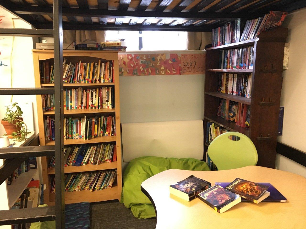 Na foto, o cantinho da leitura da Acera School. Vemos uma estante cheia de livros e um pufe. Em cima, uma cama para que as crianças possam ler.