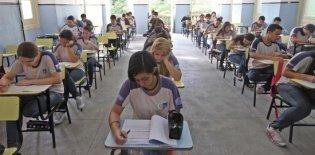 Adolescentes fazem prova em uma sala de aula
