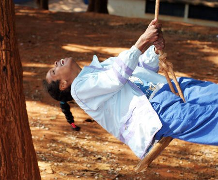 Andreia Pereira Gil, deficiente mútipla, balançando no pátio da EMEF Doutor João Alves dos Santos. Foto: Kriz Knack