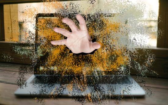 Mão atravessando tela do computador em direção ao usuário
