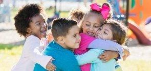 Crianças do Ensino Infantil se abraçam no pátio da escola