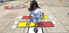 Menina brinca de pular amarelinha no pátio da escola
