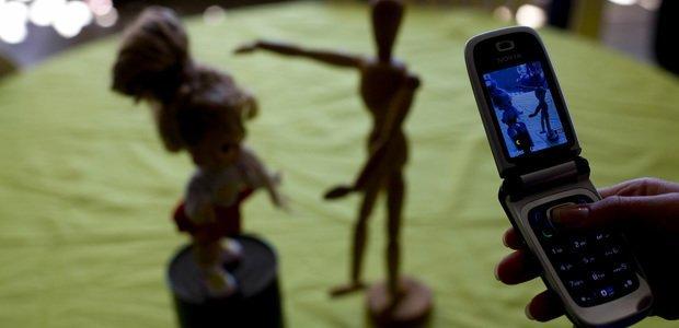 Aluno do professor Rogério Bettoni, no Instituto Efigênia Vidigal, fotografa estatuetas usando a câmera digital do celular. Foto: Leo Drumond / Agência Nitro