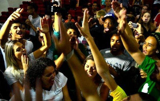 Estudantes secundaristas gritam com os braços levantados